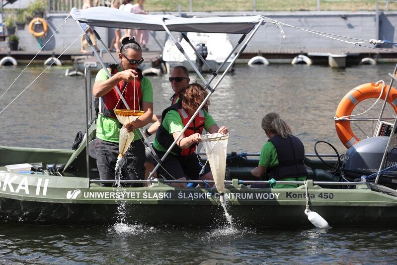 Łódź motorowa na Motławie, w środku trzy osoby trzymają w ręku worki z wodą