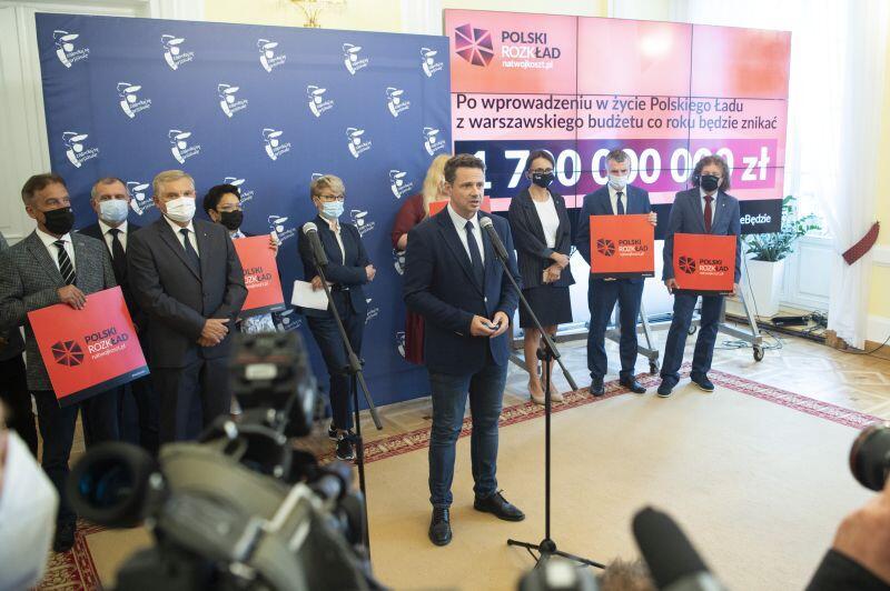 wspólne zdjęcie mężczyzn i kobiet w oficjalnych strojach na tle ekrany z napisem Polski nieŁAD, widać z boku dziennikarzy i kamery