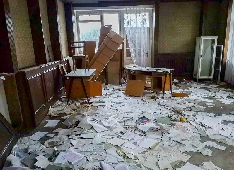 pokój z rozsypanymi na całej podłodze papierami