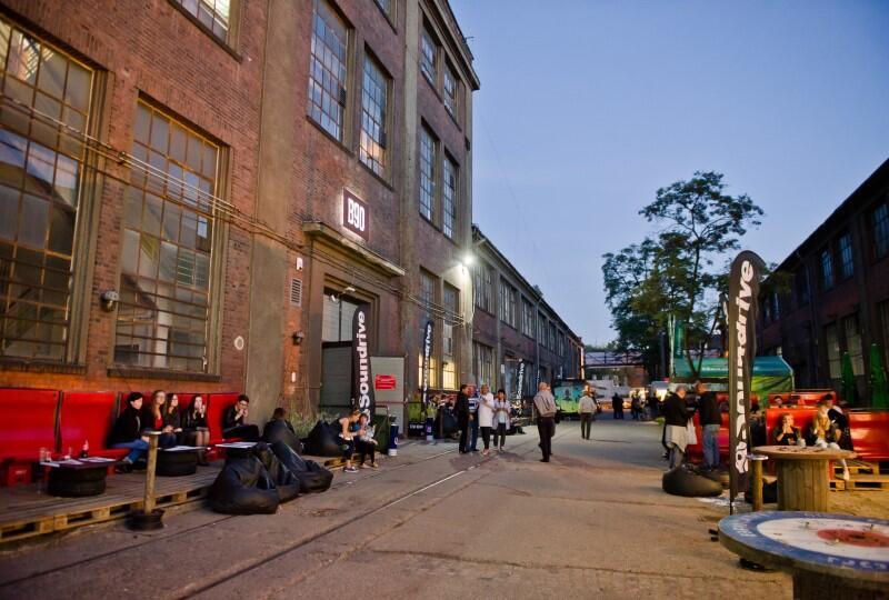 widok na ulicę stoczniową, po której spacerują ludzie, po lewej industrialny budynek z cegły