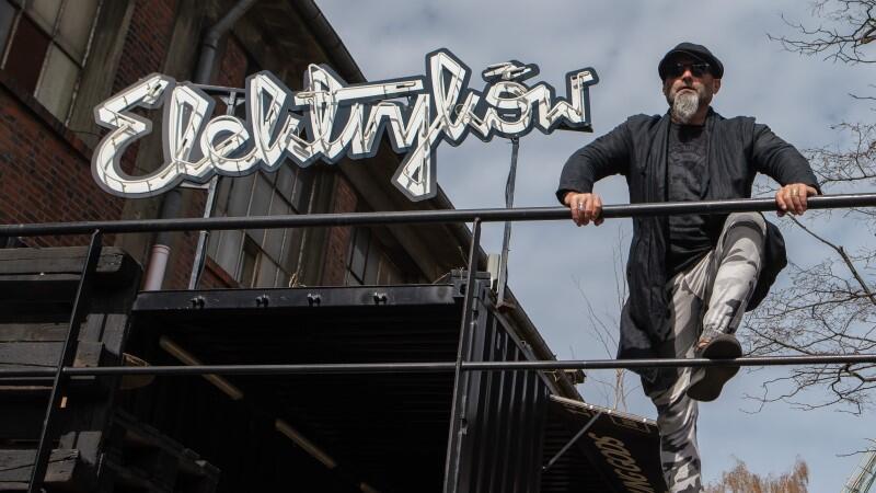 mężczyzna z brodą, w kaszkiecie opiera się o barierkę, po lewej neon Elektryków