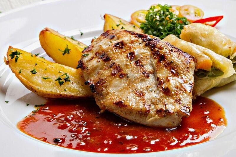 Zdjęcie przedstawia porcję obiadową na białym talerzu. Jest pieczona sztuka mięsa, podpiekane ziemniaki, krojone w łódeczki, dwa pierożki i surówka. Danie podlane sosem w kolorze czerwonym