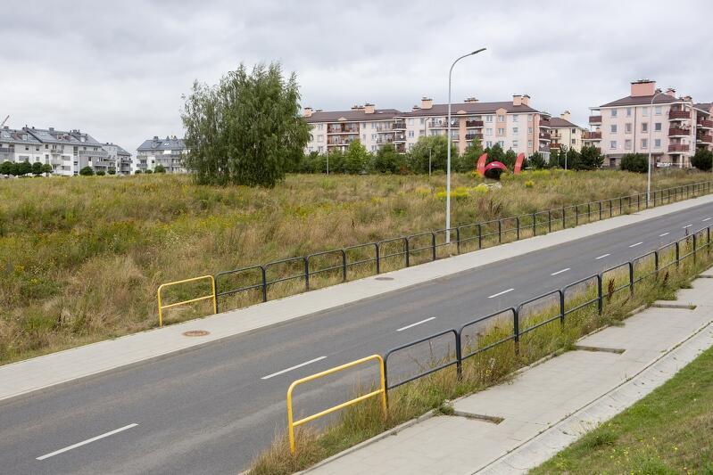 Fragment ulicy, barierki i trawa, w oddali widać zabudowania