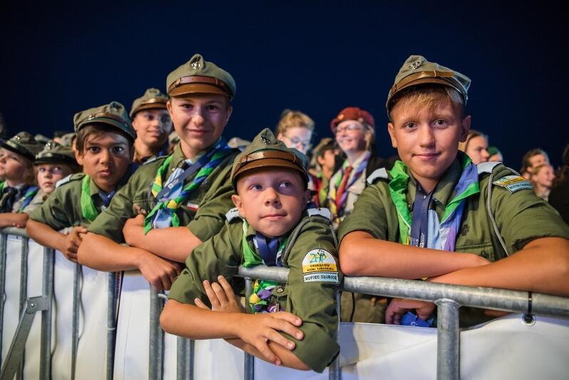 Kilka roześmianych młodych osób w mundurkach harcerskich, opierają się o barierkę
