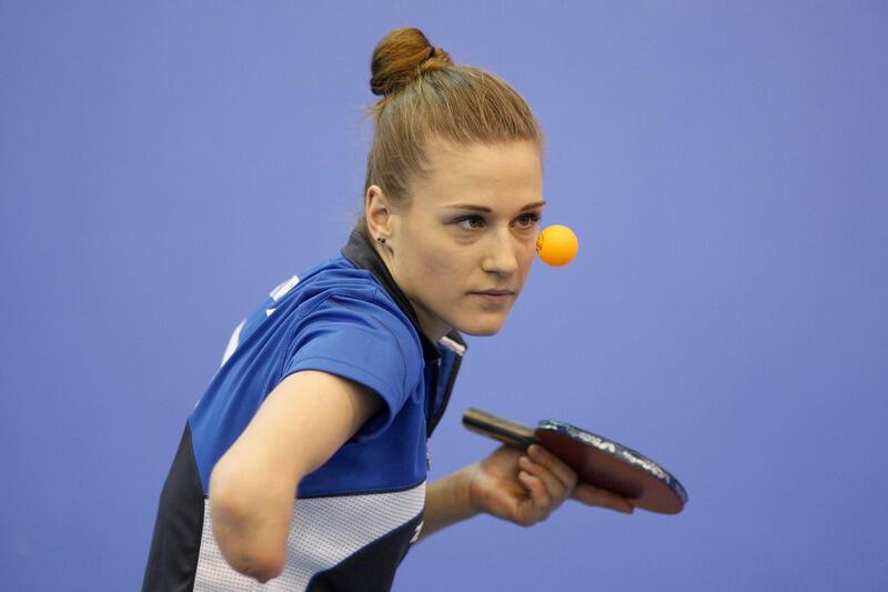 Młoda kobieta gra w tenisa stołowego, w lewej dłoni trzyma rakietkę, przed nią pomarańczowa piłeczka. Kobieta nie ma prawego przedramienia