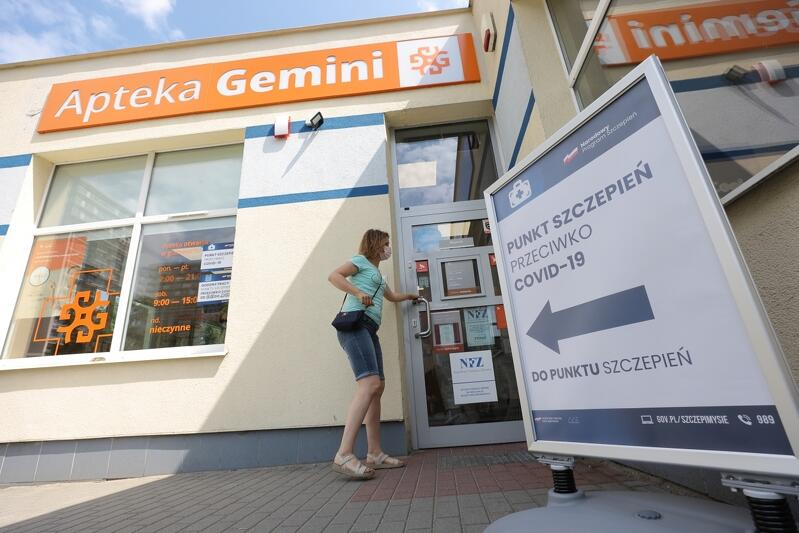 """Fragment budynku apteki z napisem Gemini, fragment reklamy z napisem """"Punkt szczepień przeciw Covid-19"""""""
