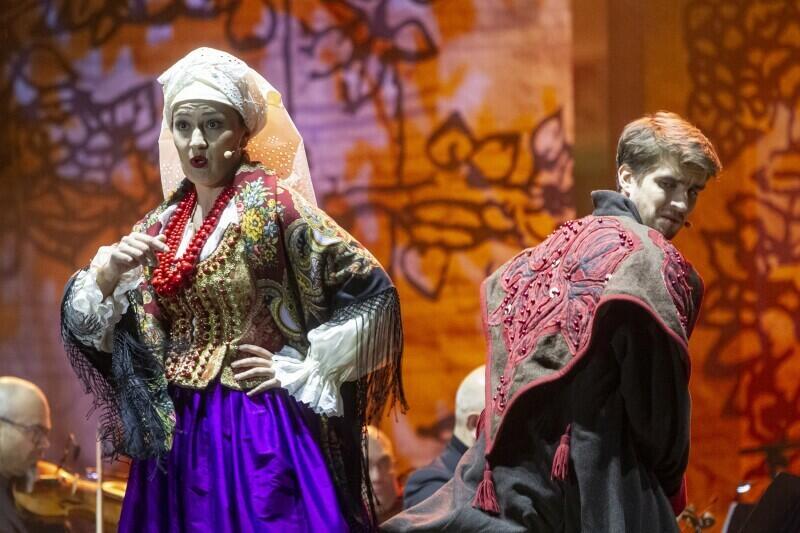 Kobieta w barwnym ludowym stroju stoi na scenie, za nią, tyłem do niej, ale spoglądający na nią przez ramię z grymasem mężczyzna