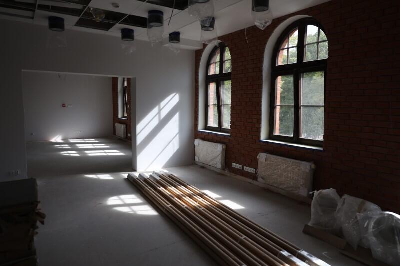 Wnętrze starego, zabytkowego budynku z półkolistymi oknami, na podłodze leżą rury