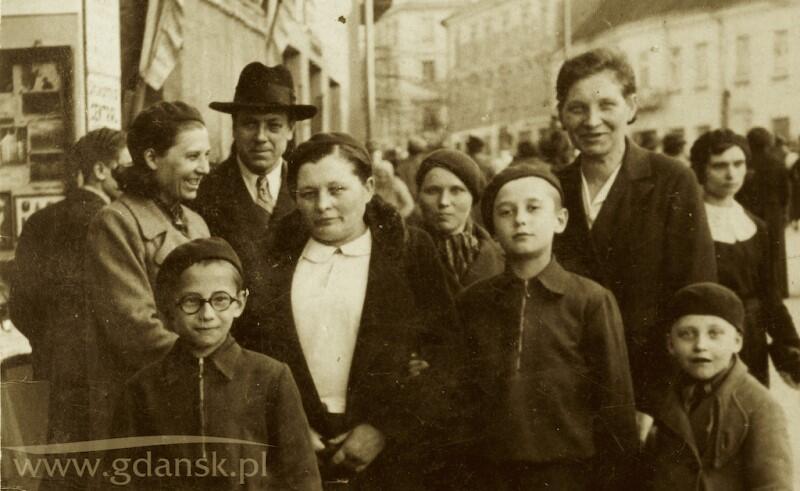 Grupa osób pozująca do zdjęcia na ulicy. Zdjęcie jest stare, czarno-białe