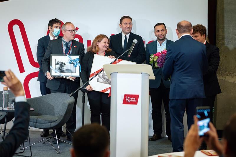 Sześć osób - mężczyźni i jedna kobieta w średnim wieku, elegancko ubrani, stoją, dwoje z nich trzyma w rękach   obrazy. Tyłem stoi mężczyzna w garniturze