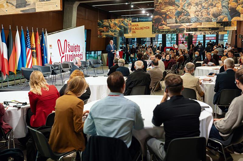 Na pierwszym planie stoliki przy nich tyłem siedzą ludzie w różnym wieku. Na scenie mężczyzna w garniturze ozed mikrofonem. Z lewej strony flagi Polski, Uni Europejskiej, Litwy Ukrainy, Niemiec