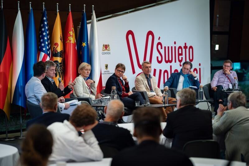 Siedzi siedem osób, dwie kobiety i pięciu mężczyzn, z lewej strony m.in. flagi Polski, Unii Europejskiej, Ukrainy