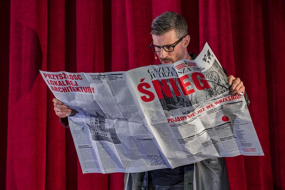mężczyzna w okularach trzyma rozpostartą gazetę z napisem śnieg, w tle czerwona kurtyna