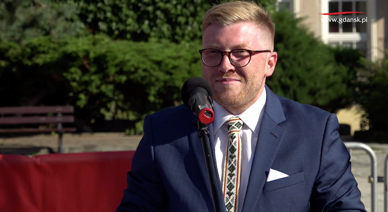 uśmiechnięty rudy mężczyzna w okularach, elegancko ubrany, stoi przed mikrofonem