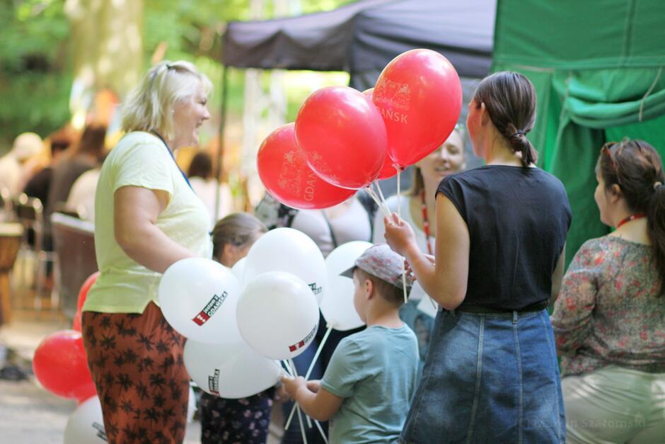 Dwie młode kobiety stoją w parku, trzymają kolorowe balony, w środku stoi kilkoro dzieci, trzymają w rękach balony