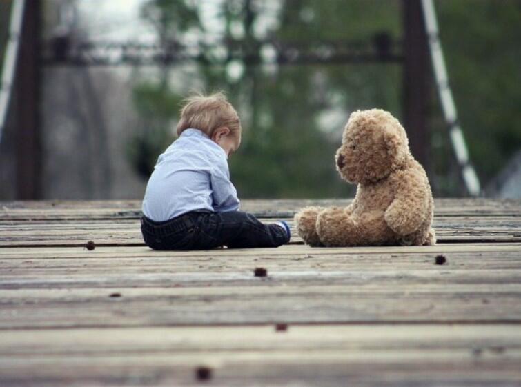 Na drewnianej podłodze w parku siedzi mały chłopczyk naprzeciwko niego siedzi miś-zabawka