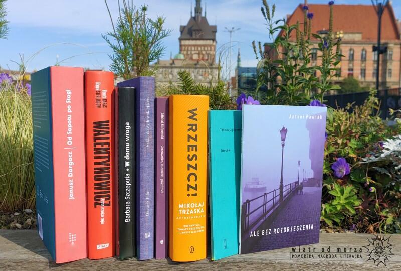 komplet książek na tle zabytkowych budynków Gdańska