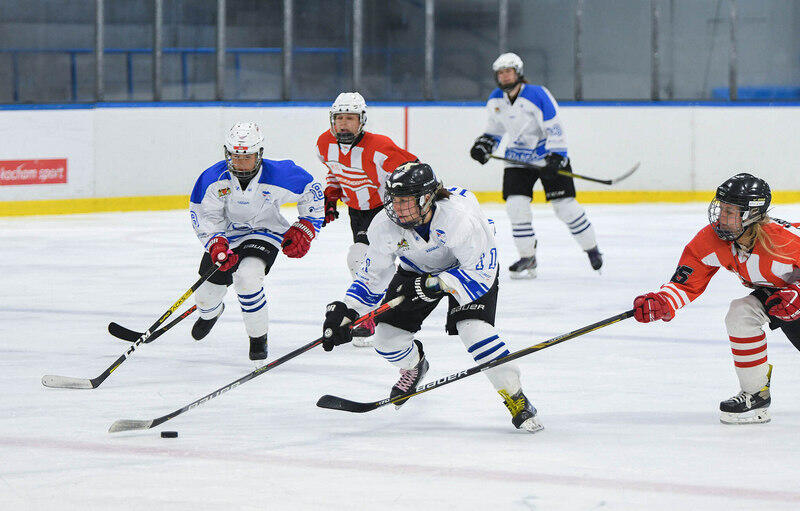 Kobiety w strojach hokejowych na lodzie: pięć zawodniczek, trzy w białych koszulkach, dwie w czerwonych. Na pierwszym planie dwie walczą o krążek, mają wyciągnięte dłonie z kijami. Pozostałe są w tle