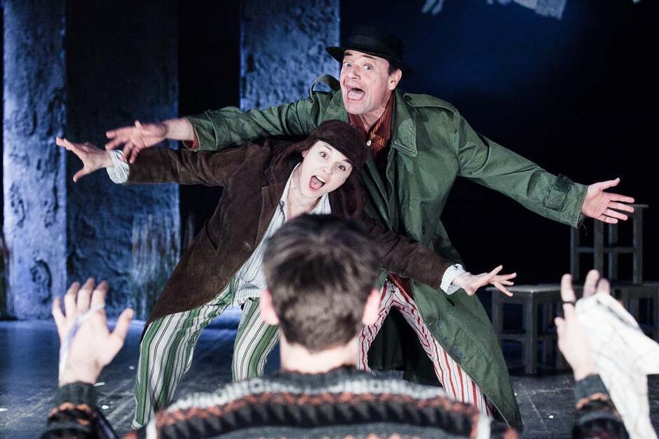 aktor w zielonym płaszczu i brązowym kapeluszu ma szeroko otwarte usta i rozpostarte ramiona, przed nim aktorka w brązowej marynarce i czapce, w podobnej pozycji
