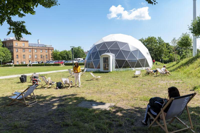 futurystyczny duży namiot na polanie, w tle duży ceglany budynek, na polanie leżaki, kilka osób