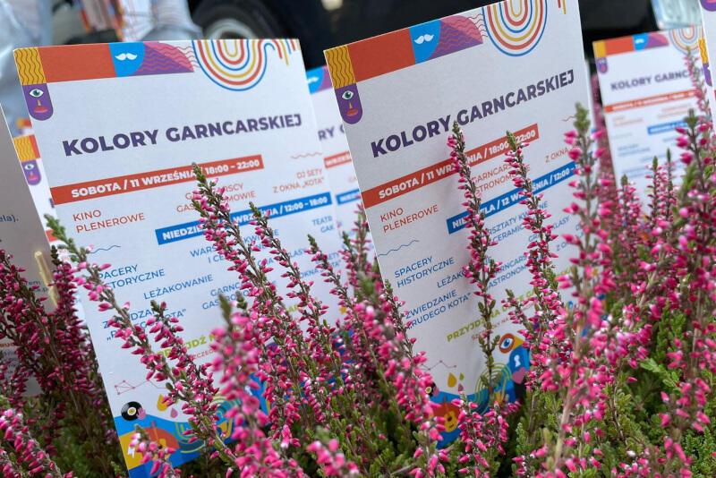 ulotki z napisem kolory garncarskiej i programem sfotografowane w otoczeniu różowych wrzosów