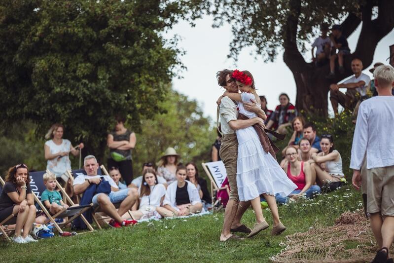 Fragment parku, na trawie siedzą ludzie w różnym wieku, w środku młoda dziewczyna ubrana na biało w ramionach młodego chłopaka