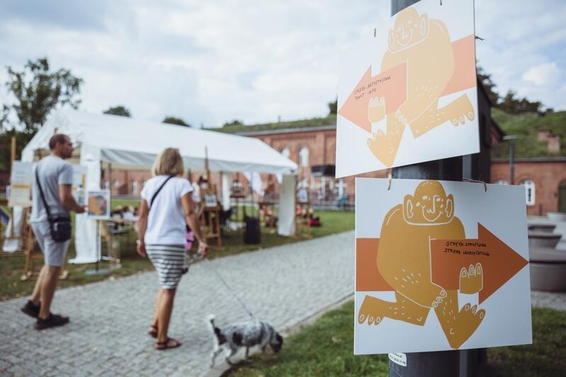 Centrum Hevelinaum, plakaty ze Stolemem, scieżką idzie dwójka ludzi