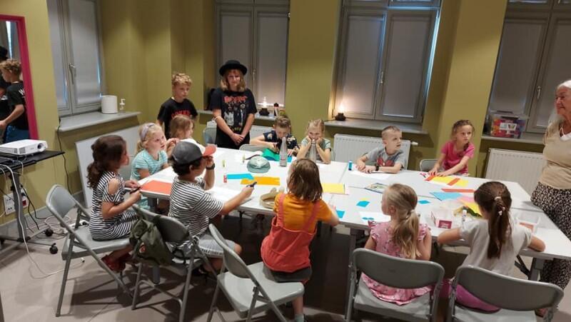 Duży stół, przy nim siedzi kilkoro dzieci, malują
