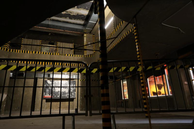 Ciemne wnętrze fragmentu budynku, cegły, odpadnięty tynk na ścianach, barirki zabezpieczające