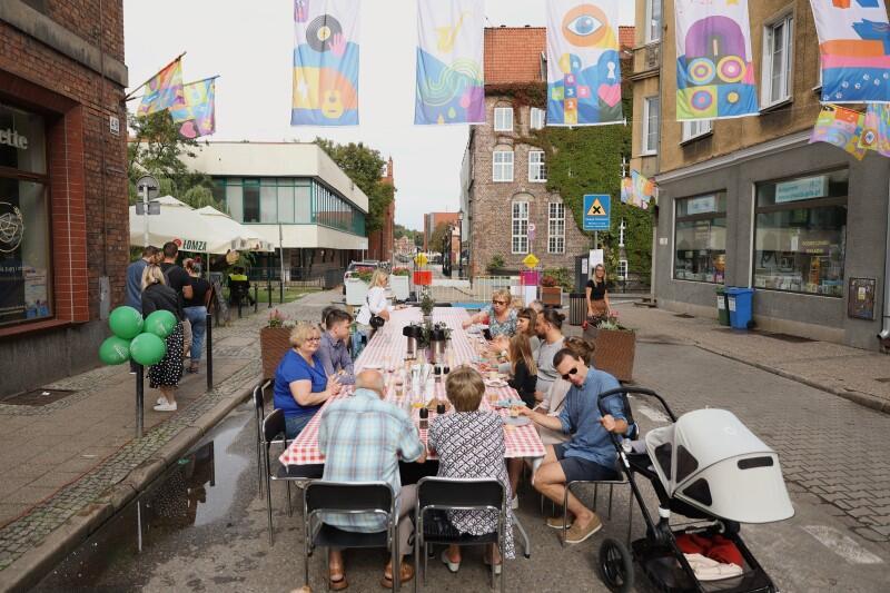 Fragment ulicy Garncarskiej, na ulicy stoi długi stół wokół kilka osób w różnym wieku, na stole naczynia, potrawy. Po chodnikach po obu stronach przechodzą pojedyncze osoby.
