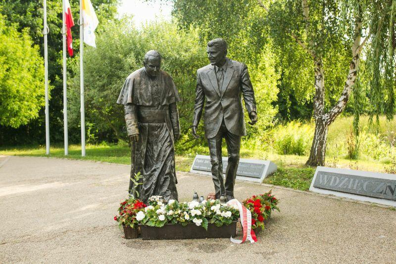 Fragment parku, w środku pomnik przedstawiający dwóch idących obok siebie mężczyzn: jeden z nich to Ronald Reagan, drugi papież Jan Paweł II
