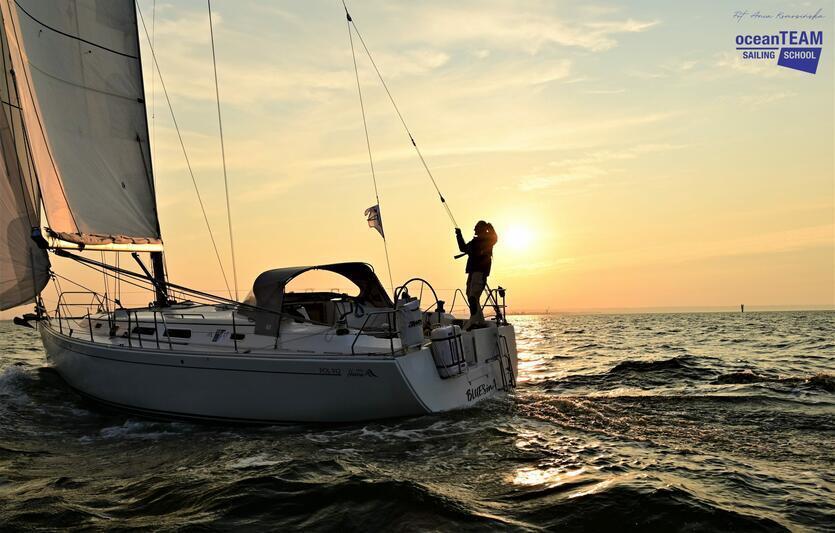 jacht płynący na morzu, wtle zachód słońca