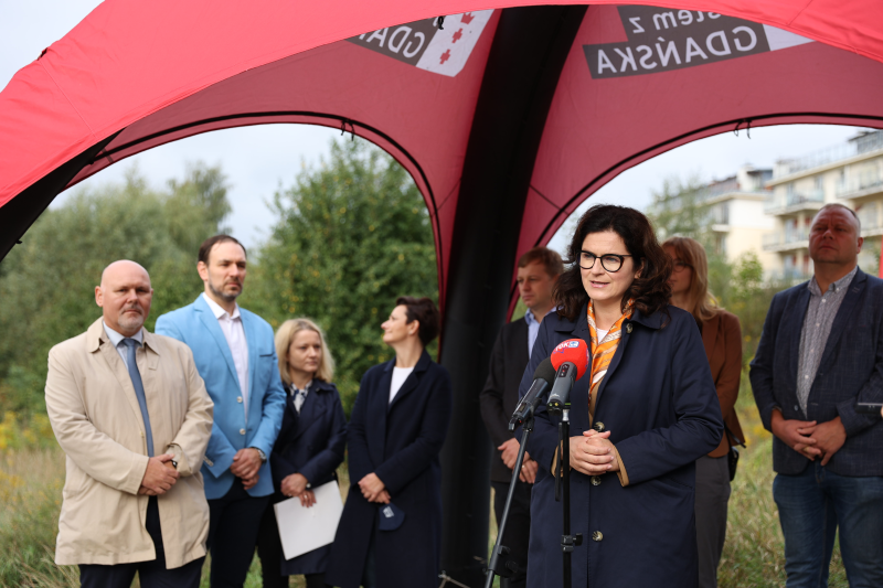 Osiem osób elegnacko ubranych w różnym wieku stoi pod namiotem na trawie. Po prawej stronie kobieta w średnim wieku stoi przed mikrofonem
