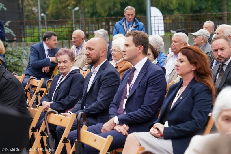 Rząd krzeseł pod gołym niebem, na których siedzi kilka osób w eleganckich strojach - młoda kobieta po prawej i patrząc w lewo - dwaj mężczyźni, a następnie starsza kobieta. Za nimi na krzesłach jest więcej osób