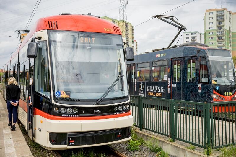 Widzimy dwa tramwaje stojące obok siebie na równoległych torowiskach. Na pierwszym planie jest nowoczesna Pesa w korystyce czerwono kremowej, za nią stoi zabytkowy czarno-czerwony Constal z lat 80. ubiegłego stulecia