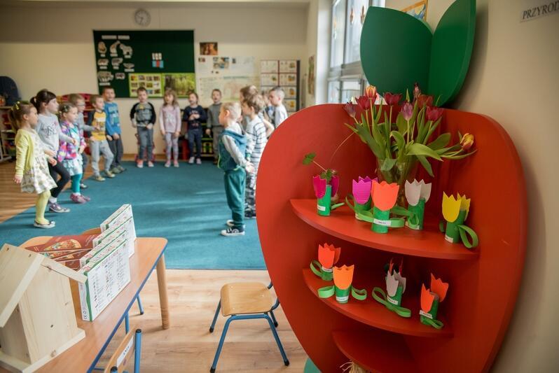 Sala przedszkolna, na pierwszym planie kolorowa półka z kwiatami z papieru, w oddali stoją dzieci