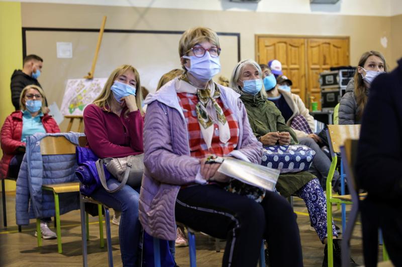 Kilkanscie osób w różnym wieku siedzi na krzesłach, mają maseczki na twarzy