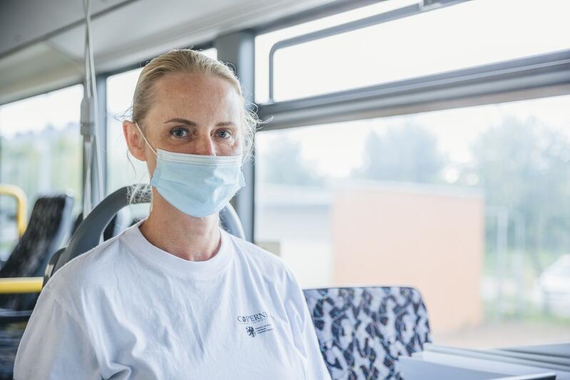 Kobieta w średnim wieku, blond włosy, ma maseczkę na twarzy, siedzi w autobusie
