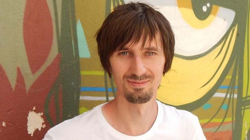 Zdjęcie przedstawia pociągłą twarz młodego mężczyzny - bruneta, który ma włosy średniej długości, a także krótkie wąsy i bródkę