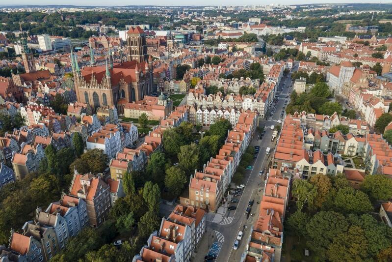 Widok z góry: dachy domów, szeregi budynków poprzecinane ulicami. W środku z lewej ponad innymi wystaje Bazylika Mariacka