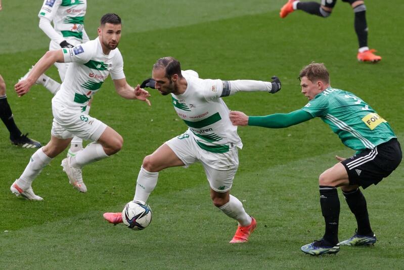 Piłkarz w białym stroju przy piłce, za nim jego kolega z drużyny. Po bokach zawodnicy w zielonych koszulkach