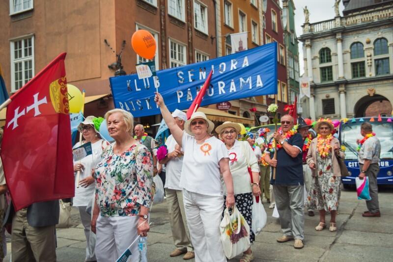 Duża grupa seniorów kolorowo ubranych i radosnych podczas ulicznej parady. Maja kolorowe baloniki i flagi Gdańska. Jest też niebieski transparent z napisem Klub Seniora. Zdjęcie zrobiono na poczatku ul. Długiej, w pobliżu Złotej Bramy