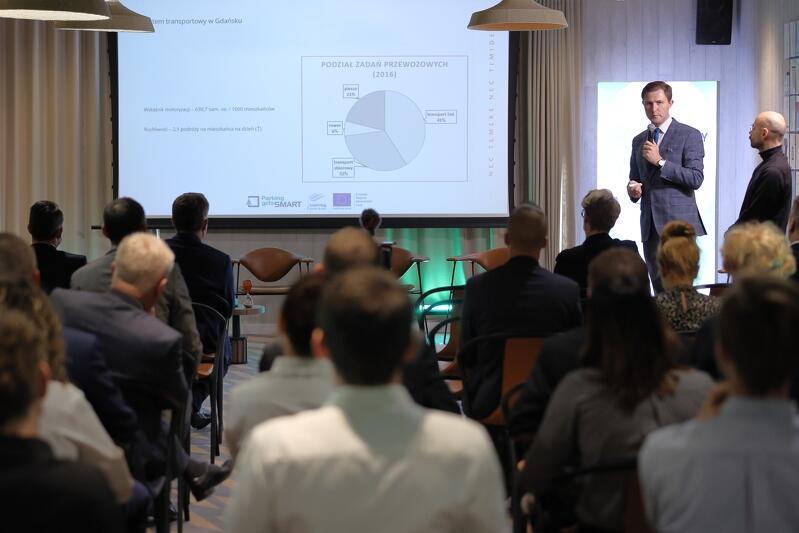 Sala konferencyjna, krzesła, siedzą na nich ludzie, w tle ekran, przy nim stoi meżczyzna
