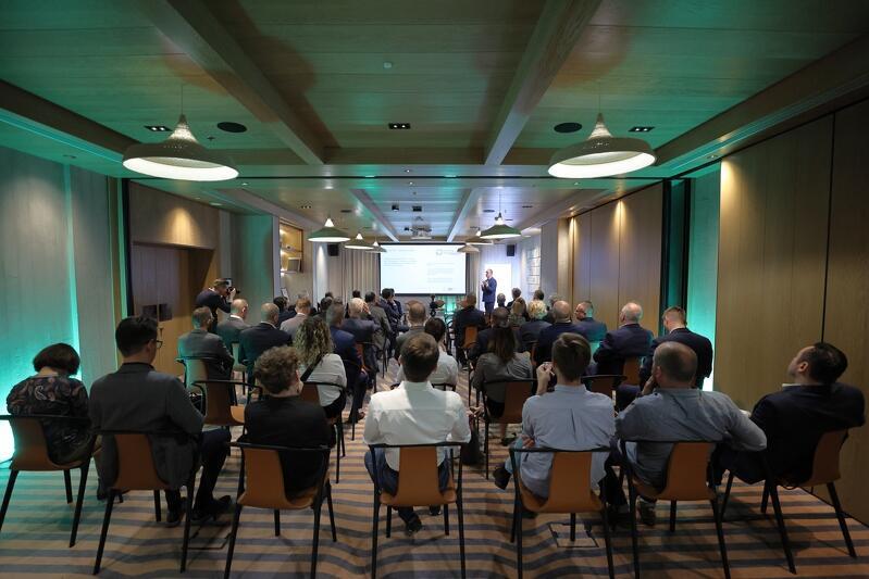 Sala konferencyjna, krzesła, siedzą na nich ludzie, w tle ekran