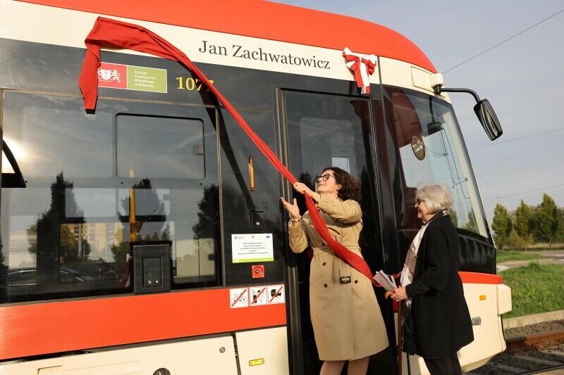 Widzimy z boku przednią część tramwaju, ustawionego w prawo. Przed wejściem do tramwaju stoją dwie kobiety. Wyższa i młodsza jest po lewej, uniesioną ręką ciągnie czerwoną szarfę, która zaczepiona jest dość wysoko, nad drzwiami tramwaju. W czynności tej pomaga starsza i niższa kobieta, która stoi za młodą, trzymając w rękach końcówkę szarfy