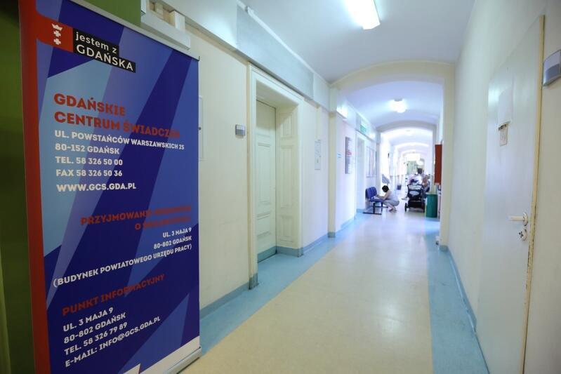 Korytarz, po lewej stronie drzwi i plansza z napisem Gdańskie Centrum Świadczeń