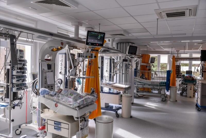 Sala szpitalna, sprzęt medyczny, łóżeczko niemowlęce, w środku leży niemowle