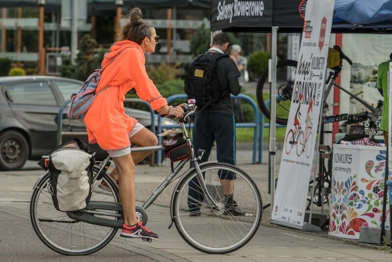 Młoda kobieta w krótkich spodenkach jedzie na rowerze