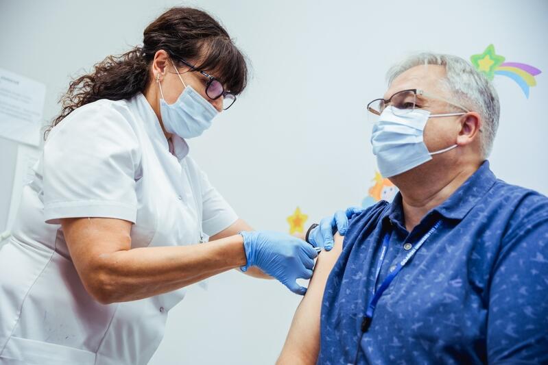 Mężczyzna w średnim wieku siedzi na kozetce szpitalnej z prawej strony, obok stoi pielęgniarka ze strzykawkę, igłę wkłuwa w jego ramię