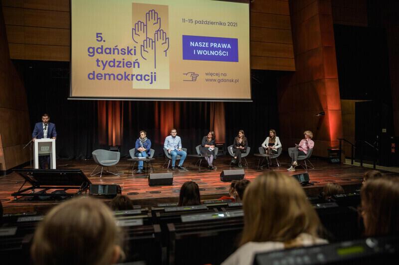 Siedem osób na scenie. Skrajnie po lewej przy mównicy stoi mężczyzna. Patrząc w prawo widzimy jeden pusty fotel, a następnie pięć foteli, zajętych kolejno: przez dwóch mężczyzn i trzy kobiety oraz jednego mężczyznę